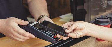 Persona pagando con el móvil por TPV