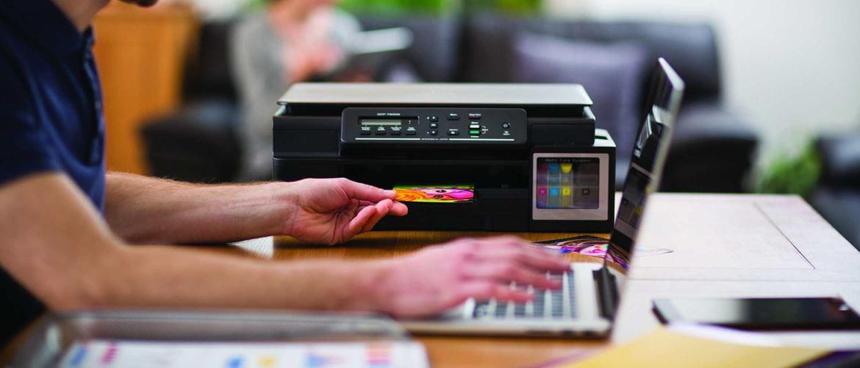 Chico joven imprimiendo foto a color desde portátil