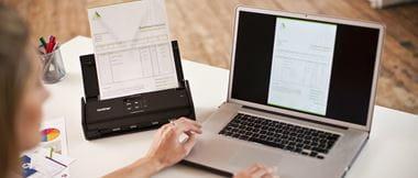 Mujer escaneando documento frente a portátil