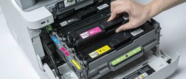 Persona cambiando tóner en impresora Brother
