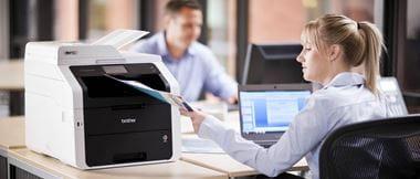 Mujer rubia en oficina recogiendo documento de impresora