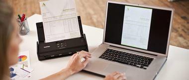 Mujer escaneando documento y enviando a portátil