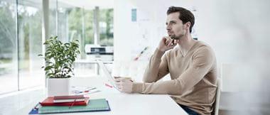 Hombre pensativo frente a portátil