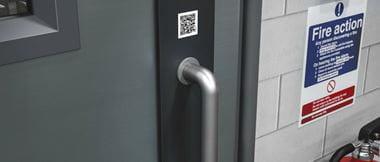 Código QR encima de tirador de puerta
