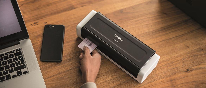 Escáner documental Brother junto a teléfono móvil y portátil