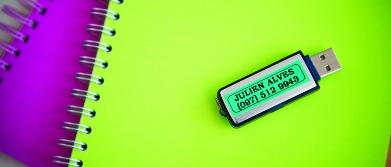 Memoria USB etiquetada encima de cuadernos