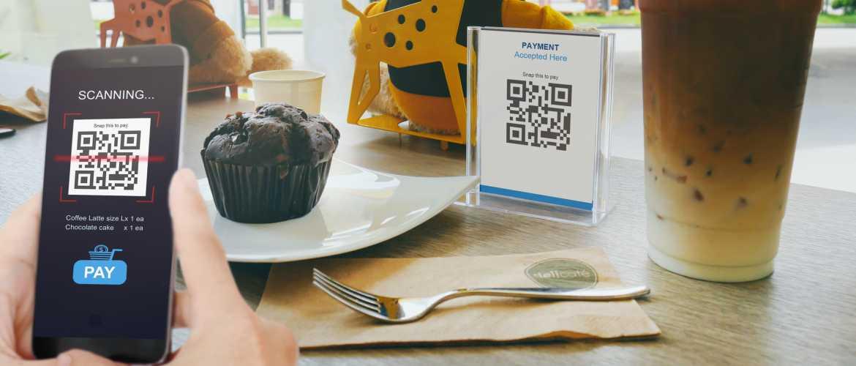 Persona escaneando código QR en cafetería