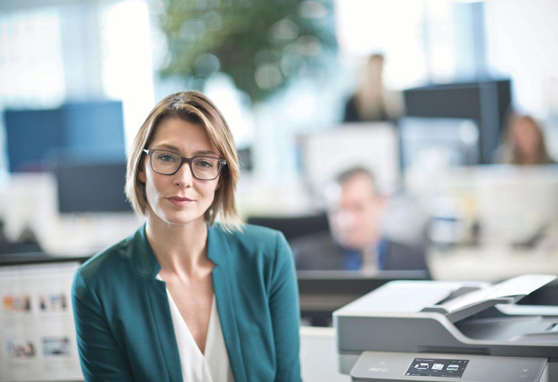Mujer con gafas junto a impresora Brother