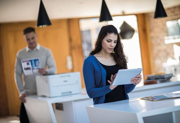 Mujer utilizando tablet y hombre detrás junto a impresora Brother