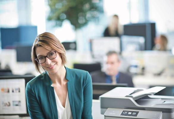Mujer con chaqueta verde junto a impresora multifunción Brother