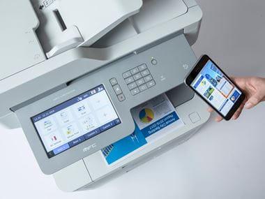 Impresora multifunción color MFC-L957CDW Brother junto a teléfono móvil