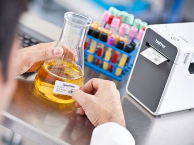 Etiquetas para botes de muestras junto a impresora de etiquetas TD