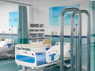 Habitación de hospital con etiqueta Brother en la puerta