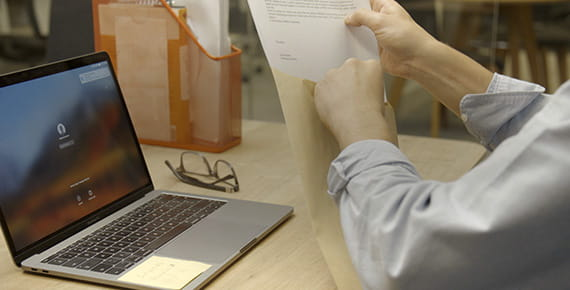 Mujer frente a ordenador portátil guardando documentos en un sobre