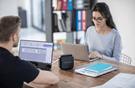 Hombre y mujer con ordenadores portátiles e impresora de etiquetas RJ Brother
