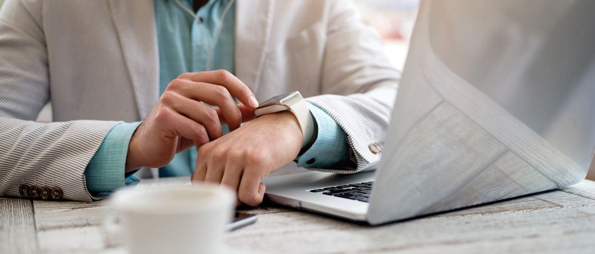 A man sitting next to his office laptop is wearing a grey suit and blue shirt. He checks his wearable technology smartwatch.