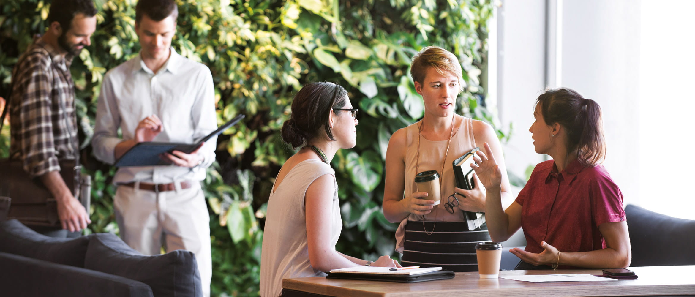 Two men and three women are holding an informal business meeting in the workplace of the future that features a prominent living green wall of plants within the office environment.