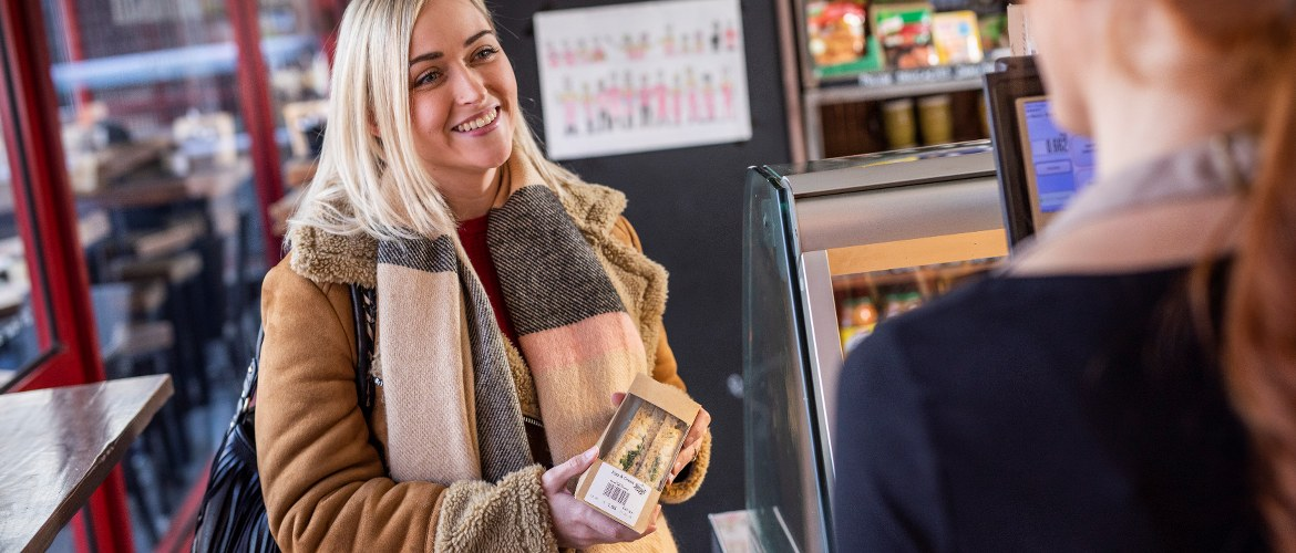 A blonde haired young woman wearaing an autumnal coat and scarf is buying a pre-prepared, clearly labelled sandwich from a retail deli shop. The customer is being served by a female member of the store's staff behind the till.