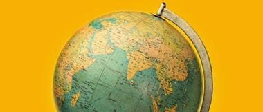 A model globe with a map of the world in front of an orange background