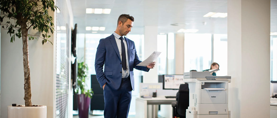 mono laser comes of age man stood by printer reading paper in office