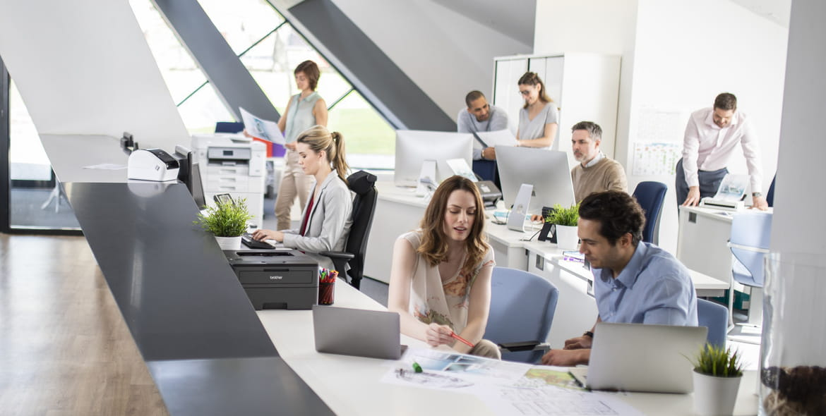 modern office with workers at laptops and having meetings