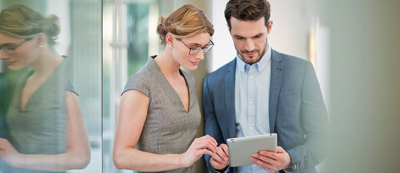 Man and woman looking at screen on tablet