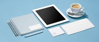 The essential tools of a mobile or freelance office worker are laid out neatly across a pale blue desk: A paper pad, tablet computer, espresso coffee cup, pens and note pads.