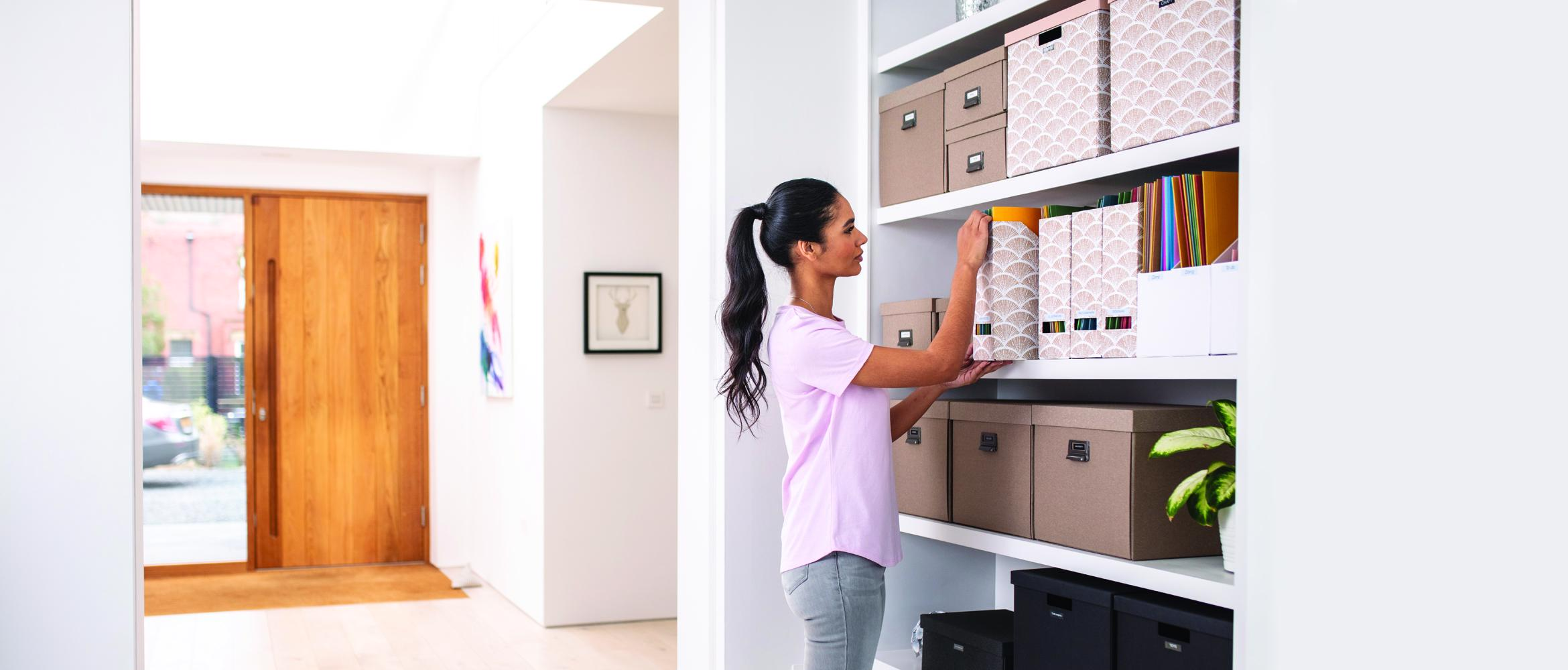 A female staff member is working from a home office / hybrid working. She is organising her paper files using a labelling printer to increase business productivity.