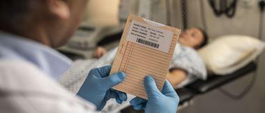 Lääkärillä on kädessään potilaskansio, jonka etiketti sisältää viivakoodin sekä tiedot potilaasta.