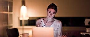 En kvinne sitter hjemme og søker på en datamaskin