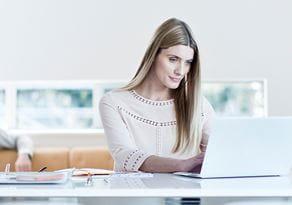 En kvinne sitter ved et bord med en datamaskin