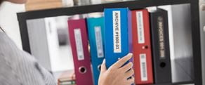 En person plasserer en blå perm som er merket med Brother TZe-tape inn i en hylle