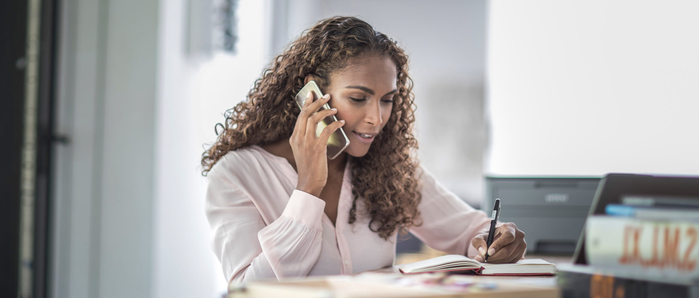 Professionally dressed woman at her desk speaking on her mobile phone and taking notes with Brother printer in background