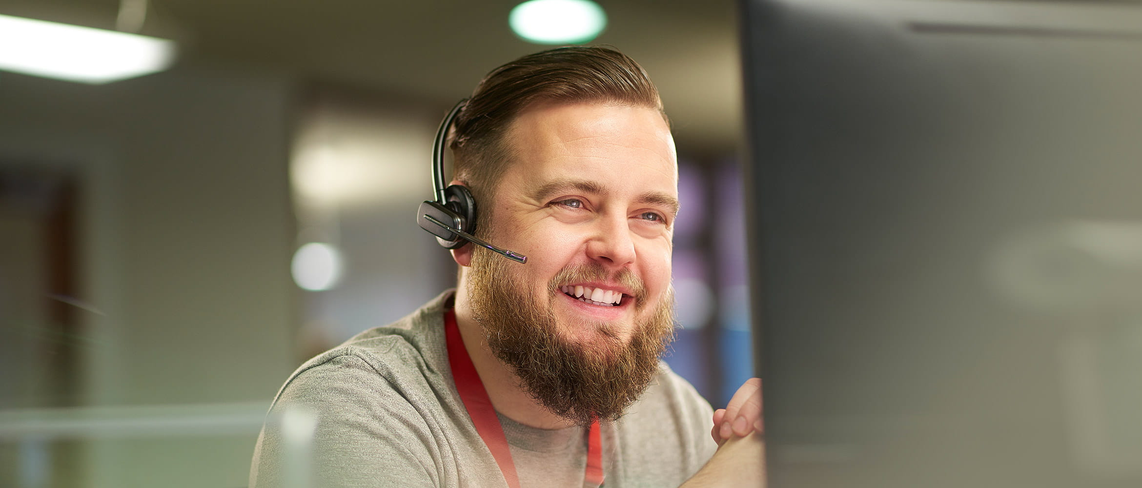 Smiling man talking on a hands free headset and looking at a computer