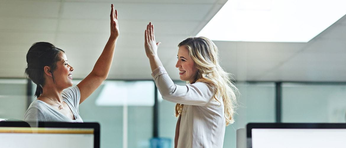 Two women high fiving and smiling at their desks