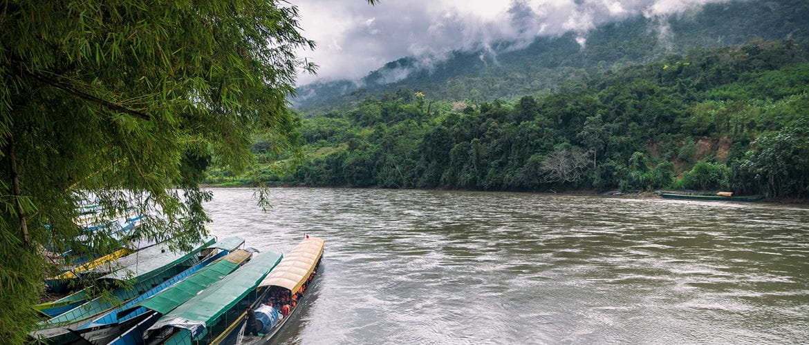 River in between mountains with boats on the side