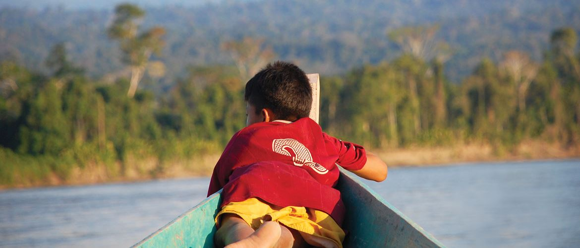 Young boy laid in boat on vast river