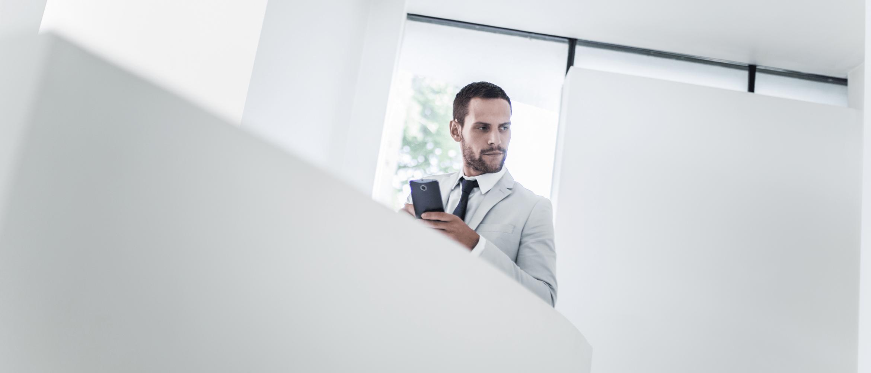 Muž v bílém obleku s mobilním Android telefonem se rozhlíží s balkónu