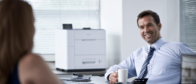 Usmívající se pracovník ve velkopodnikové kanceláři s tiskárnou HL-S7000DN na stole
