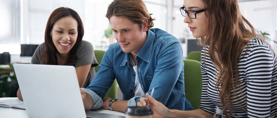 Three young colleagues work together on a laptop
