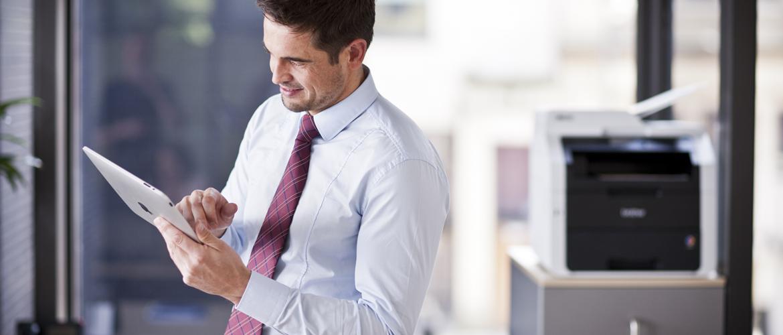 Obchodní pracovník v kanceláři pracuje na tabletu s tiskárnou MFC-9340CDW v pozadí