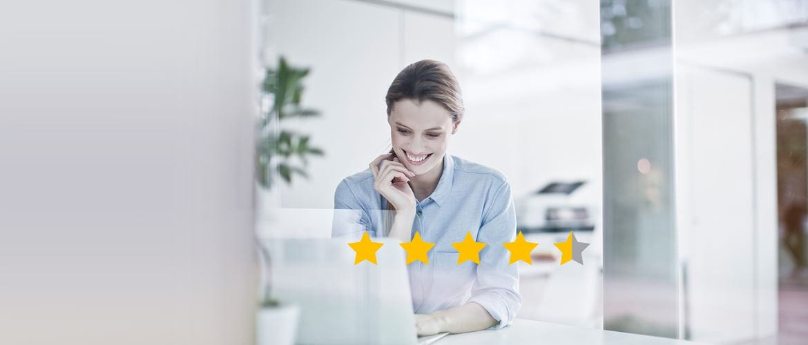 Women on a laptop leaving a review with star ratings in front of her