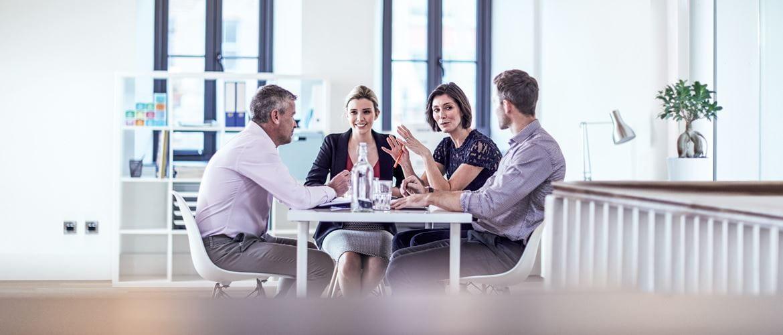 Dva muži a dvě ženy u stolu v kanceláři