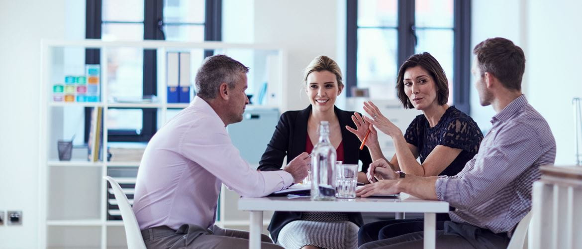 Two business women and two business men sat at a table discussing a matter