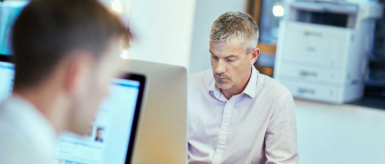 Uzņēmējs strādā pie galda ar datoru