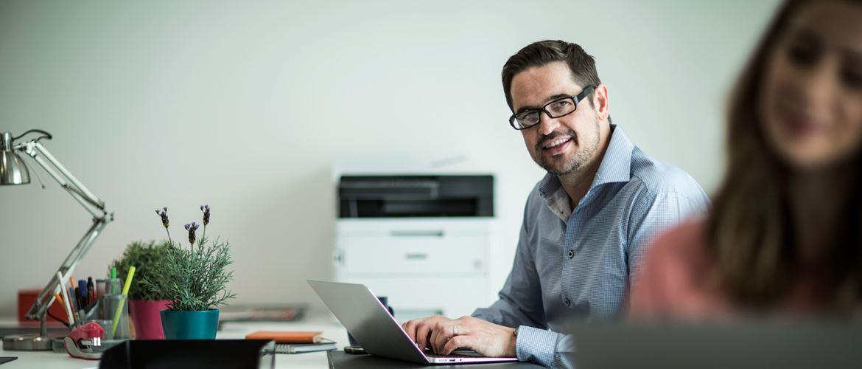Muškarac sjedi za stolom s prijenosnim računalom, u pozadini DCP-L3550CDW