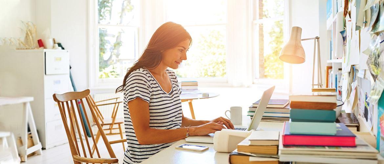 žena u prugastoj majici za stolom s prijenosnim računalom, bijelim namještajem, šarenim mapama
