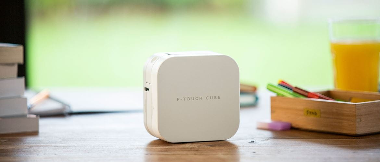 Drukarka etykiet P-touch CUBE na stole kuchennym w domu