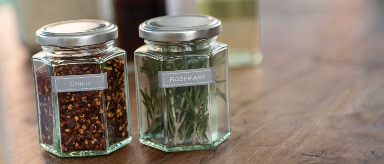 Fehér szöveg szürke címkéken, amelyet üvegeken alkalmaznak, hogy azonosítsák a chilit és a rozmaringot