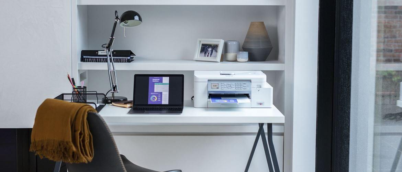 Laptop på skrivebord ved siden af printer